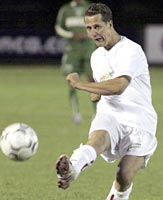 Ferrari Formula One driver Michael Schumacher, takes a free kick during the second half of a soccer match to benefit needy children in Palmeiras Stadium in Sao Paulo, October 20, 2004.