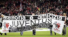 Liverpool and Juventus fans carry a banner stating the name of those killed in the Heysel Stadium disaster before their Champions League quarter-final first leg match