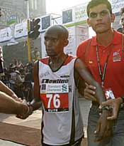 Julius Sugut is taken away for his dope test after crossing the finish line