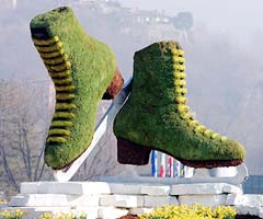 A pair of giant mossy figure skates stand outside the skating venue in Turin, Italy