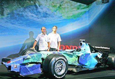 Rubens Barrichello (left) and Jenson Button, stand beside a Honda Formula One racing car.