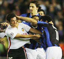 Tempers flare between Valencia's Viana Hugo (left) and Nicolas Burdisso of Inter Milan after the final whistle