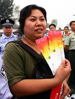 A Chinese woman displays the tickets she bought from a ticket booth after queuing for many hours in Beijing, on Friday
