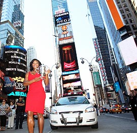US Open champion Serena Williams poses with her trophy at the Times Square in New York