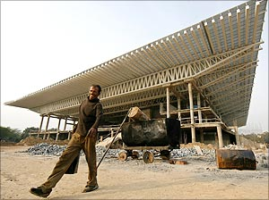 A labourer walks at the Thyagaraja Sports Complex, one of the venues for the Commonwealth Games 2010