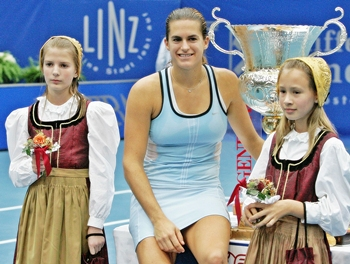 Mauresmo poses with girls in traditional outfits after winning the Generali Open in Linz