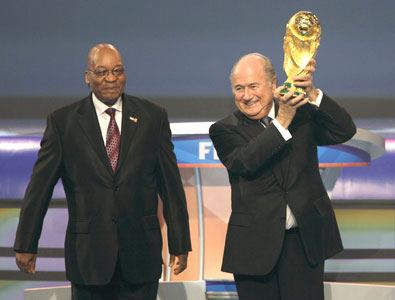 South African President Jacob Zuma watches as FIFA president Blatter holds up the World Cup trophy before the 2010 World Cup draw in Cape Town on Friday