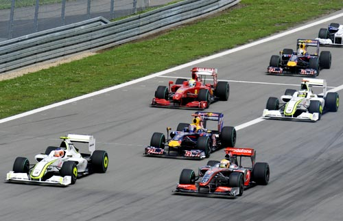 Brawn GP driver Rubens Barrichello of Brazil (left) leads the pack into the first turn ahead of McLaren's Lewis Hamilton