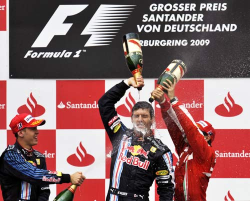 Webber is sprayed with champagne by team-mate Vettel (left) and Massa (right)