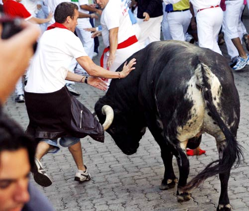 A Dolores Aguirre fighting bull charges against a runner during the fifth bull run of the San Fermin festival