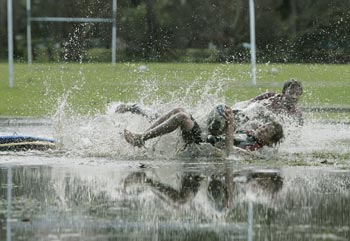 Boys play rugby on a flooded pitch in Sydney