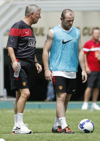 Manchester United's manager Alex Ferguson (left) and Wayne Rooney talk during a training session in Seoul on Thursday
