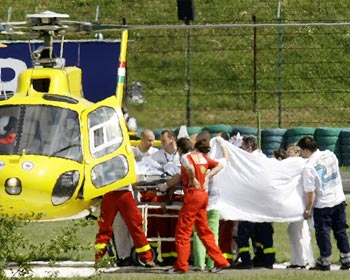 Medical staff lift Felipe Massa into a helicopter