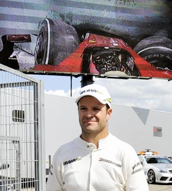 Rubens Barrichello walks past a video screen showing the Felipe Massa crash