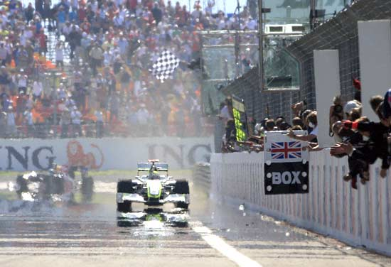 Jenson Button crosses the finish line