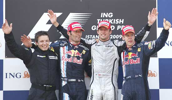 Peter Bonnington, a member of the Brawn-Mercedes team, 2nd placed Mark Webber, winner Jenson Button and 3rd placed Sebastian Vettel on the podium