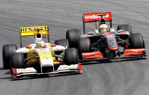 Fernando Alonso (left) overtakes Lewis Hamilton