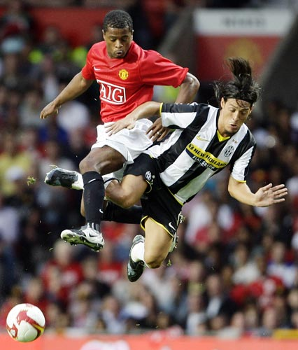 Manchester United's Patrice Evra (left) clashes with Mauro Camoranesi of Juventus
