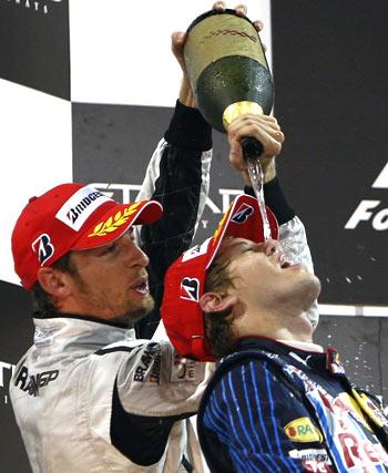 Red Bull's Sebastian Vettel and Brawn GPs Jenson Button (left) celebrate their podium finish in Abu Dhabi on Sunday