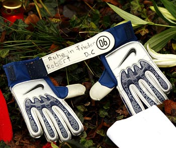 Soccer gloves with the inscription 'Rest in Peace, Robert' lie at a condolence area outside the headquarters of soccer team Hanover 96