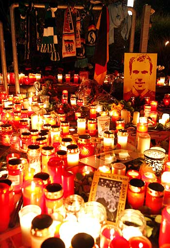 Soccer scarfs are fixed beside lit candles in memory of German goalkeeper Robert Enke outside the stadium of Hanover 96