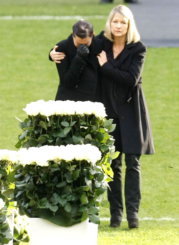 Robert Enke's wife Teresa (left) is comforted by an unidentified woman during the memorial service on Sunday