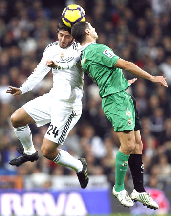 Real Madrid's Granero (left) and Racing Santander's Lacen are involved in an aerial duel during their La Liga match on Saturday