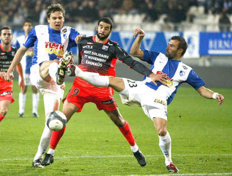 Lisandro Lopez (centre) of Olympique Lyon challenges Sandy Paillot (left) and David Sauget of Grenoble during their French Ligue 1 tie on Saturday