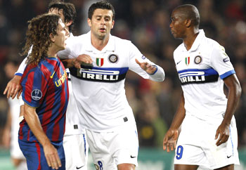 Barcelona's Carles Puyol (left) argues with former team-mate and Inter Milan striker Samuel Eto'o (right) while Thiago Motta tries to seperate them, at Nou Camp in Barcelona on Tuesday