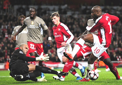 Standard Liege 'keeper Sinan Bolat saves a shot from Arsenal's William Gallas (10) in London on Tuesday