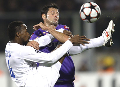 Fiorentina's Gobbi and Olympique Lyon's Govou (left) get entagled as they vie for possession during their Champions League match on Tuesday