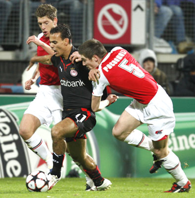 Olympiakos's Jaouad Zairi (centre) is challenged by AZ Alkmaar's Stijn Schaars and Sebastien Pocognoli (right) during their Champions League match on Tuesday