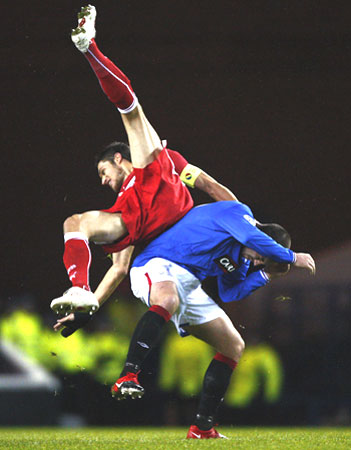 VfB Stuttgart's Delpierre falls over Rangers' Boyd during their Champions League match in Glasgow on Tuesday