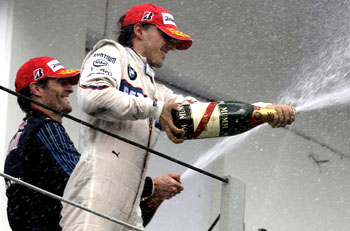 Robert Kubica (right) and Mark Webber celebrate on the podium at Interlagos