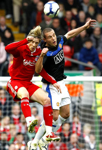Liverpool's Fernando Torres (left) and Manchester United's VIdic are involved in an ariel duel during their Premier League match on Sunday