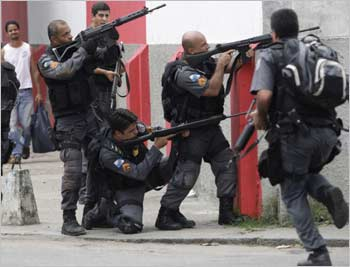 Police officers take cover during a operation against drug dealers in the Vila Cruzeiro slum in Rio.