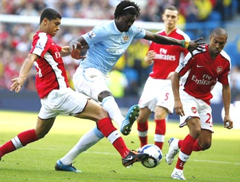 Manchester City's Adebayor is locked in a challenge with Arsenal's Denilson and Clichy