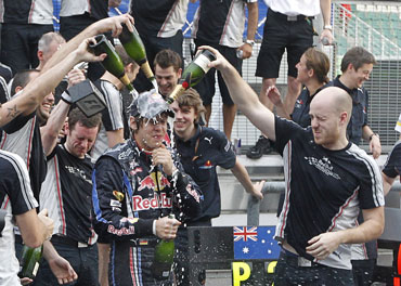 Red Bull Formula One team members pour champagne over driver Sebastian Vettel of Germany after he won the Malaysian F1 GP