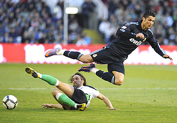 Racing Santander's Oscar Serrano Rodriguez (left) challenges Real Madrid's Cristiano Ronaldo during their La Liga match on Sunday