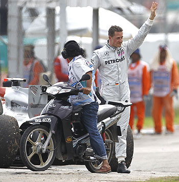 Michael Schumacher of Mercedes waves to the crowds after retiring from the Malaysian Grand Prix on Sunday