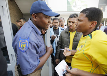 Police keep watch over South African football fans waiting to buy tickets for the 2010 FIFA World Cup