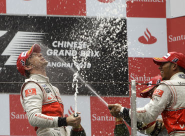 Jenson Button celebrates with Lewis Hamilton