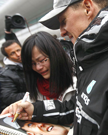 Michael Schumacher (right) signs autographs for a fan in Shanghai