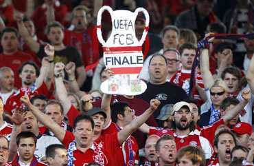 Bayern supporters hold a mock trophy during the semi-final