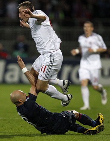 Lyon's Cris tackles Bayern's Olic during their match