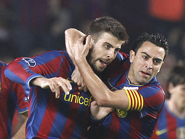 Barcelona's Pique (left) celebrates after scoring with team-mate Xavi