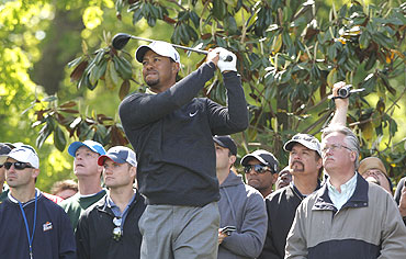 Tiger Woods tees off as the gallery watches on the 15th tee during a pro-am event before play in the Quail Hollow Championship