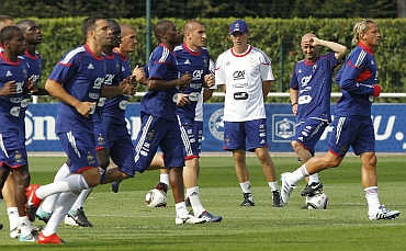 Coach Laurent Blanc (in white) watch France's soccer team players during a training session