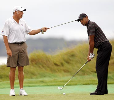 Tiger Woods hits as his caddie Steve Williams holds a club during a practice round