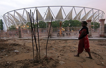A woman walks past the Jawaharlal Nehru Stadium that is still under construction
